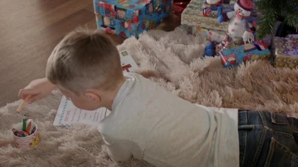 Little boy lying under christmas tree and write a letter to santa claus