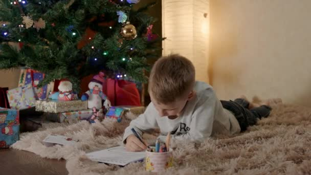 blond boy lying under the christmas tree, and writing a letter to Santa