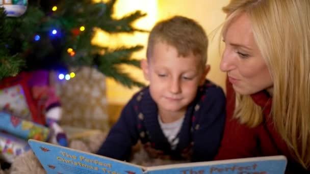 Mladá matka čtení příběh obelhat pod stromeček nový rok