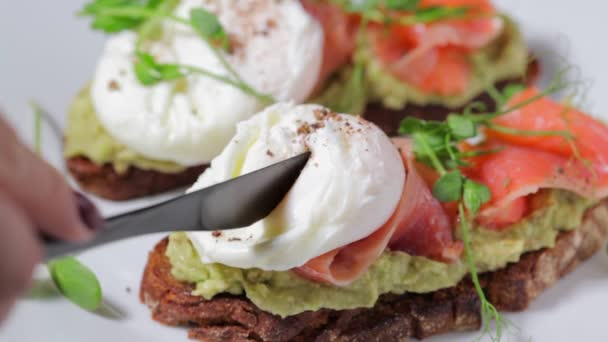 Toast with salmon, poached egg and avocado on white plate.