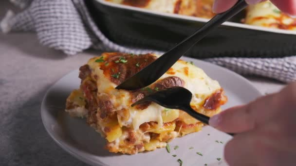 Traditional Greek moussaka - potato and meat casserole with cheese, dark background.