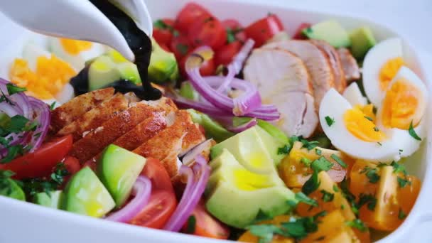 American cobb salad with chicken, avocado, egg, tomatoes and onions in white dish. American cuisine concept.