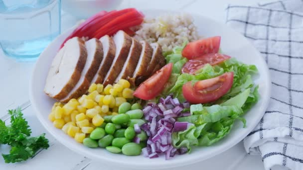 Grilled chicken breast with brown rice and vegetables in white plate, gray background, top view. Healthy food concept.