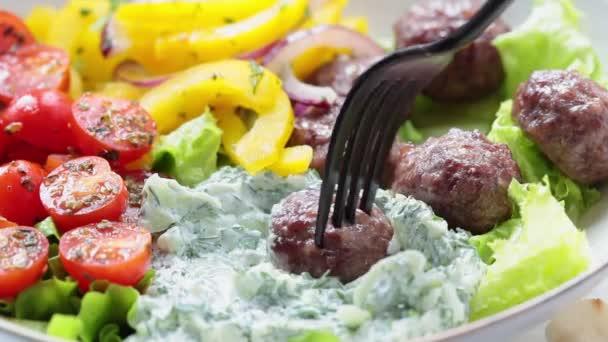 Greek meatballs, tzatziki sauce, tomato and cucumber salad.