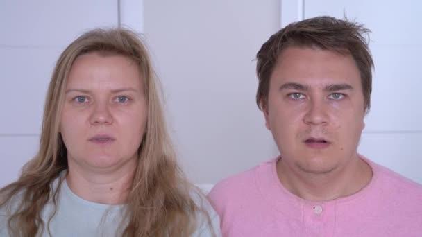 Fiatal házaspár pizsamában lát valami hihetetlent, és szinkronban tárja ki a száját sokkban otthon, elől. Az érzelmek élénk kifejeződése.