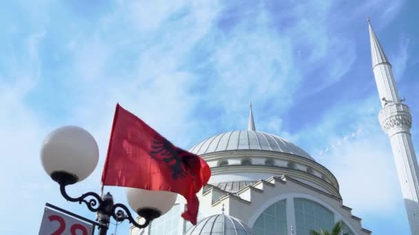 Flag of Albania flutters in the wind on warm sunny day, blue cloudy sky and beautiful white stone mosque in background. National attributes, monument of architecture.