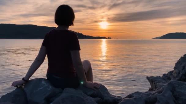 Die junge Frau sitzt vor dem Hintergrund eines farbenfrohen Sonnenuntergangs, macht ein Selfie und macht Fotos mit ihrem Smartphone, schickt ein Foto an Freunde. Schöne Meereslandschaft.