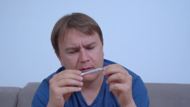 Young Caucasian man rolls a joint and inhales the aroma of cigarette, front view. Medical marijuana for chronic pain control, as muscle relaxant, for treating glaucoma and other health problems