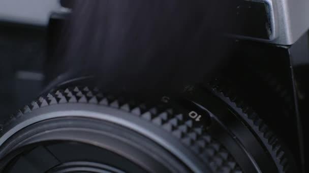 Reinigung von Staub von Vintage-Fotokameras mit schwarzer Bürste.