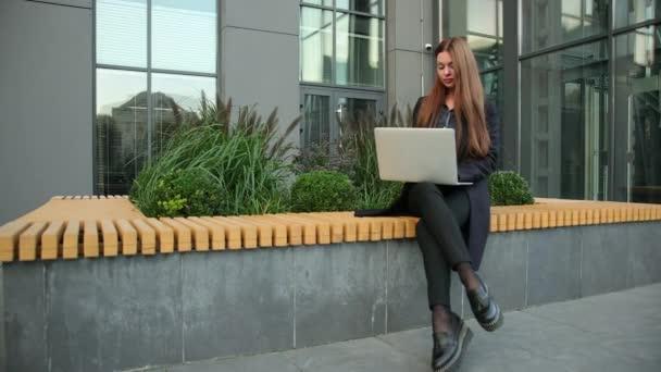 Az üzletasszony laptopot használ az irodaház ellen. Kaukázusi üzletasszony