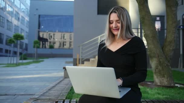 Figyelmes nő, aki egy laptopon ül az utcán. Üzletasszony.
