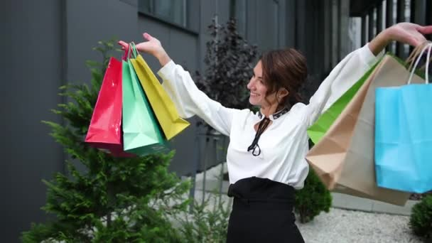 A woman holding several colorful shopping bags. Pretty millennial model lady