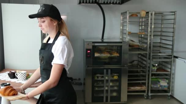 Prodavač podávající croissant a cappuccino v kavárně. Mladá žena pekárna