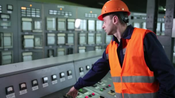 Arbeiter drücken Tasten auf der CNC-Maschinensteuerungsplatine in der Fabrik. Jungingenieur