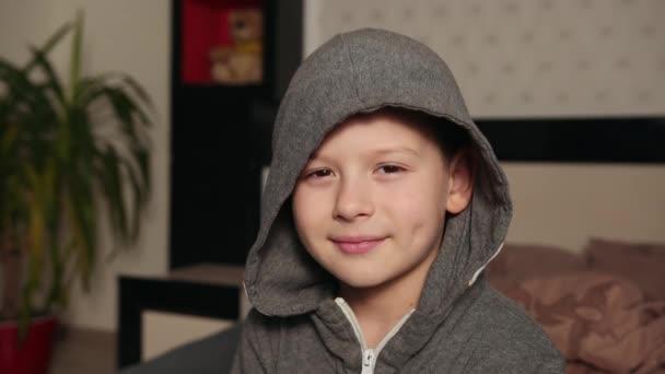 Mosolygó iskolás fiú, arckép egy tinédzser fiúról, aranyos fiatal, boldog gyermek portré