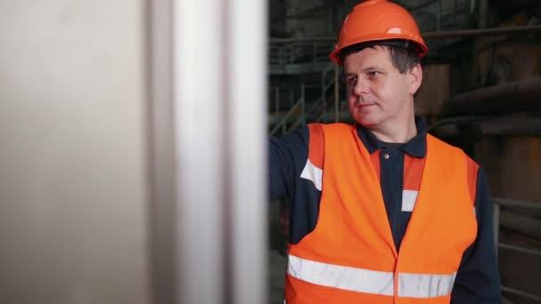 Ingenieur steht vor Industriemaschine und drückt einen Knopf