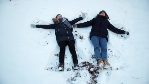 Girl and a guy lying on the snow in winter. Lie in snow, move their arms, legs,