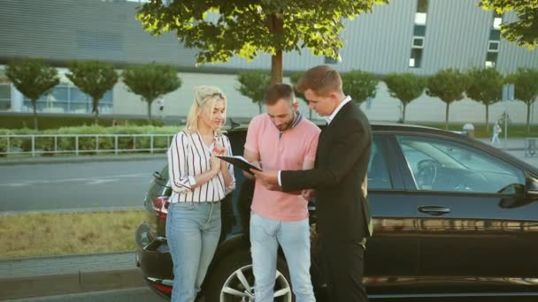 Seller sells the car to happy young couple. Men shaking hands beautiful vehicle.