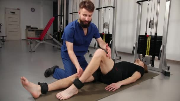 Male patient in hospital physical therapy concept. Therapist treating young man
