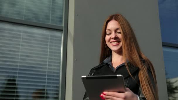 Geschäftsfrauen nutzen digitale Tablets außerhalb des Büros. Braune Haare weiblich im Gespräch