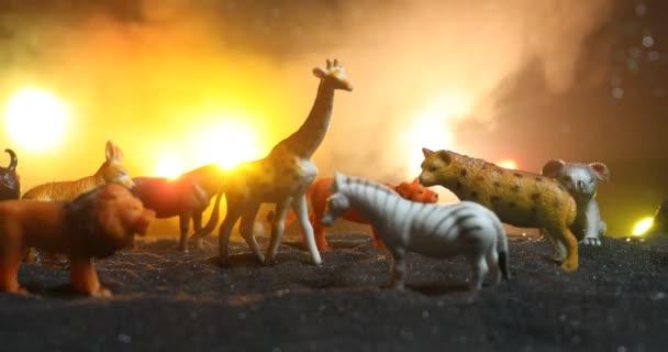 Nahaufnahmen von Tierfiguren auf dunklem Hintergrund mit buntem Gegenlicht, Wilderei-Konzept