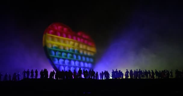 lgbt rights concept, Silhouette of crowd standing against a heart painted like a LGBT flag in dark background. Selective focus