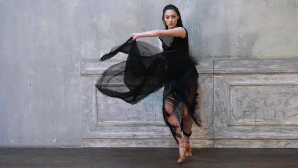 Woman dancer in motion with a cloth against the wall