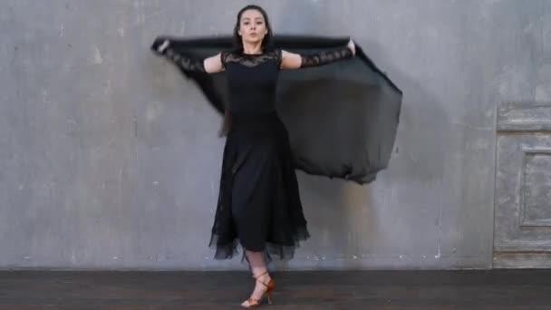 Női táncos mozgásban egy ruhával a falnak támasztva. Táncterem tánc.