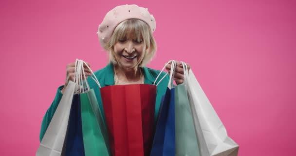 Portré kaukázusi idős nő boldog arcát viselő svájci sapka, álló elszigetelt fölött rózsaszín fal stúdió kezében sok színes bevásárló táskák nézelődő vásárlások. Vásárlási koncepció