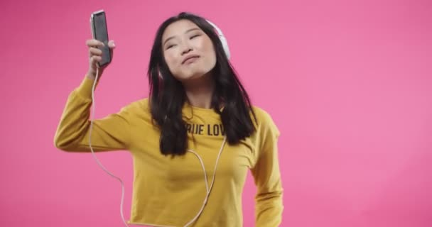 Portrait. Cheerful happy young Asian beautiful teen woman listening to songs in headphones on smartphone and dancing to music moving rhythmically isolated on pink rosy background. Fun concept