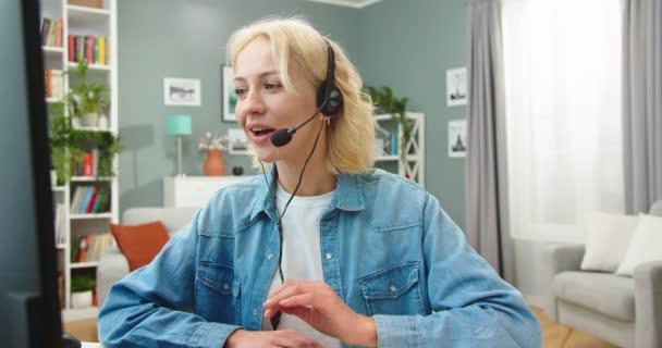 Fröhliche junge blonde Frau mit Kopfhörer, die per Webcam beim Webinar-Training am Computer Notizen macht, Studentin, die in einer Videokonferenz telefoniert und online lernt, E-Coaching, Kundenbetreuung