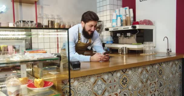 Charming Caucasian man standing behind bar and using digital smartphone in coffeehouse. Adult male barista typing messages and looking at camera. Small business, social media, technologies cooncept.