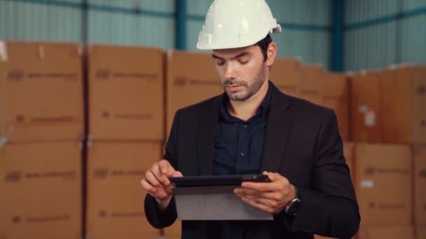 Manažer továrny používající tablet ve skladu nebo továrně