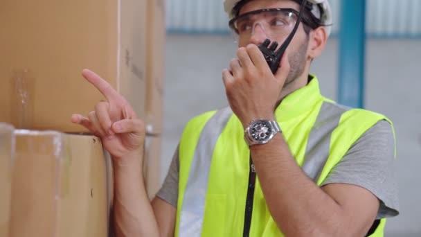 Professioneller Frachtarbeiter spricht über Mobilfunk, um einen anderen Arbeiter zu kontaktieren