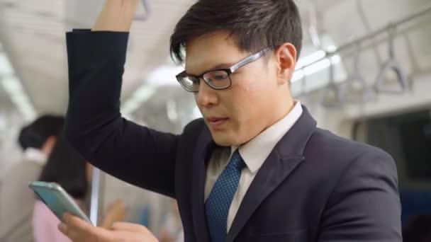 Geschäftsmann benutzt Handy in öffentlicher Bahn