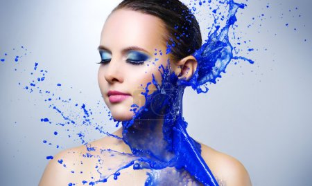 Beautiful girl and blue paint splashes