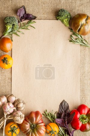 Vegetables and herbs with empty recipe blank on a sackcloth