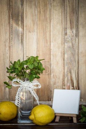 Photo pour Menthe dans un vase en verre, citrons et mini chevalet avec toile vierge sur un fond en bois - image libre de droit