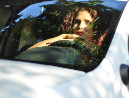 Photo pour Portrait de jeune belle brunette caucasienne femme dans sa voiture blanche cherche ennuyé. réflexion urbaine sur la fenêtre. concept de trafic jam, concept négatif émotion humaine - image libre de droit