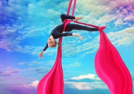 child hangs upside down on aerial silks in rainbow sky