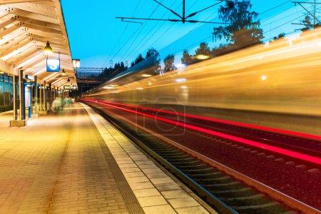 Photo pour Concept d'affaires abstrait créatif de l'industrie ferroviaire du voyage et du transport : vue d'été en soirée du train de banlieue à grande vitesse partant de la plate-forme de la gare avec effet flou du mouvement - image libre de droit