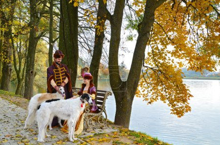 Couple in medieval costumes with borzoi dogs