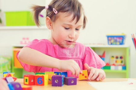 Little girl playing with toy bricks at school