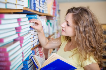 Photo for Portrait of clever student with books in college library - Royalty Free Image
