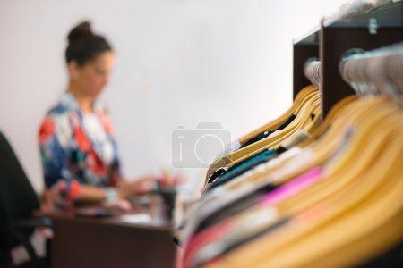 Photo pour Variété de vêtements suspendus sur étagère en boutique - image libre de droit