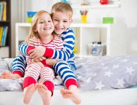 Photo pour Deux heureux frères et sœurs en rayé sleepwears au lit - image libre de droit