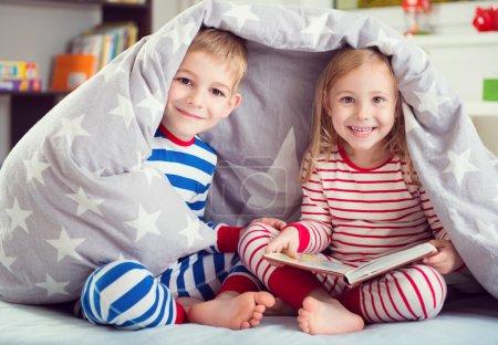 Photo pour Deux frères et sœurs heureux lire livre sous le couvercle - image libre de droit