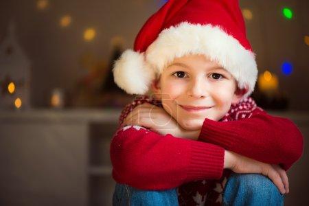 Cute little boy in red hat waiting Santa Claus