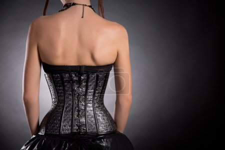 Rear view of gothic girl in silver leather corset
