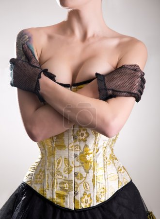 Attractive cabaret girl in corset embracing herself